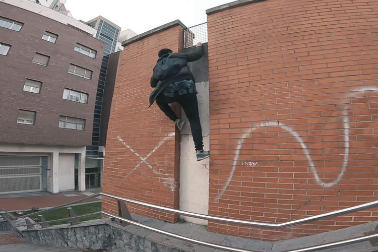 explorador urbano escalando muro