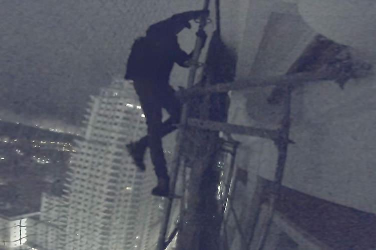 explorador urbano escalando andamio